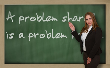 halved: Successful, beautiful and confident woman showing A problem shared is a problem halved on blackboard Stock Photo