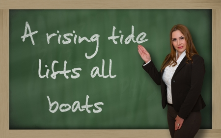 Successful, beautiful and confident woman showing A rising tide lifts all boats on blackboard