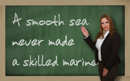 mariner: Successful, beautiful and confident woman showing A smooth sea never made a skilled mariner on blackboard