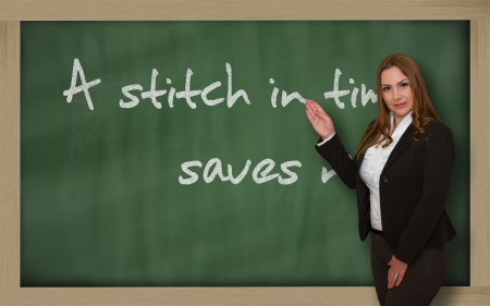 Successful, beautiful and confident woman showing A stitch in time saves nine on blackboard
