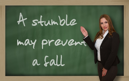 to stumble: Successful, beautiful and confident woman showing A stumble may prevent a fall on blackboard