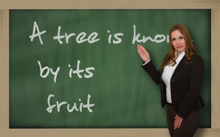 Successful, beautiful and confident woman showing A tree is known by its fruit on blackboard Stock Photo