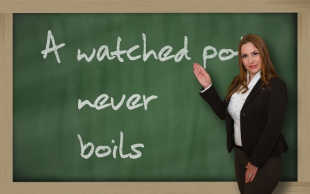 Successful, beautiful and confident woman showing A watched pot never boils on blackboard