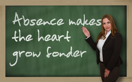 wriiting: Successful, beautiful and confident woman showing Absence makes the heart grow fonder on blackboard