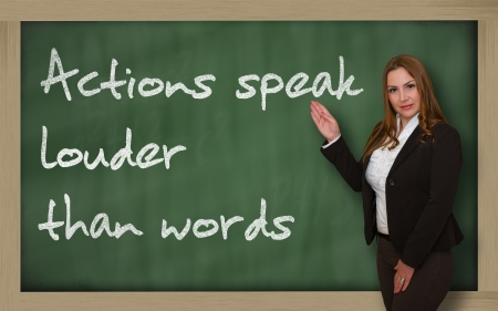 wriiting: Successful, beautiful and confident woman showing Actions speak louder than words on blackboard