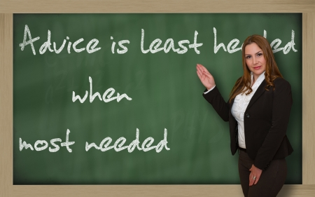 wriiting: Successful, beautiful and confident woman showing Advice is least heeded when most needed on blackboard