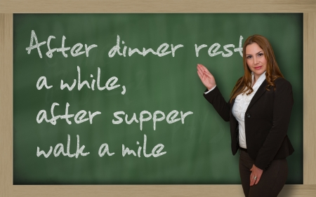 mile: Successful, beautiful and confident woman showing After dinner rest a while, after supper walk a mile on blackboard Stock Photo