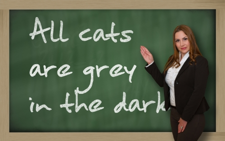 Successful, beautiful and confident woman showing All cats are grey in the dark on blackboard