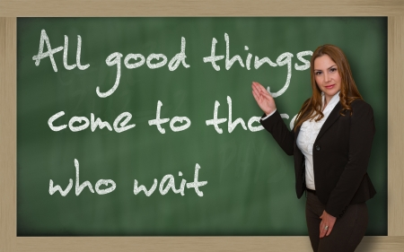 those: Successful, beautiful and confident woman showing All good things come to those who wait on blackboard