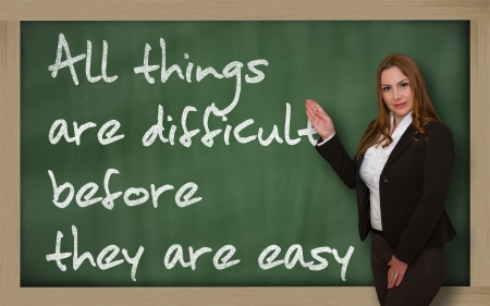 Successful, beautiful and confident woman showing All things are difficult before they are easy on blackboard Stock Photo