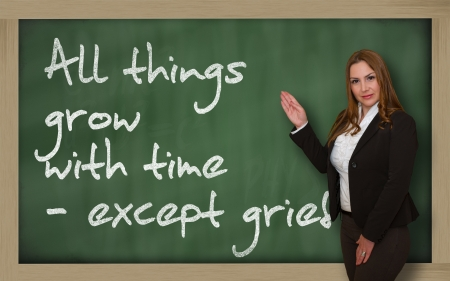 wriiting: Successful, beautiful and confident woman showing All things grow with time - except grief on blackboard