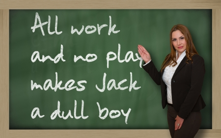 dull: Successful, beautiful and confident woman showing All work and no play makes Jack a dull boy on blackboard