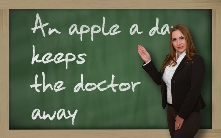 wriiting: Successful, beautiful and confident woman showing An apple a day keeps the doctor away on blackboard