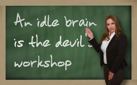 holgaz�n: Mujer exitosa, bella y segura mostrando un cerebro ocioso es el taller del diablo en la pizarra