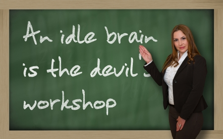 Successful, beautiful and confident woman showing An idle brain is the devils workshop on blackboard Stock Photo