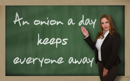 keeps: Successful, beautiful and confident woman showing An onion a day keeps everyone away on blackboard Stock Photo