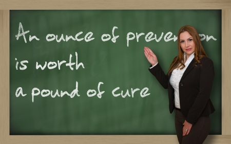 Successful, beautiful and confident woman showing An ounce of prevention is worth a pound of cure on blackboard