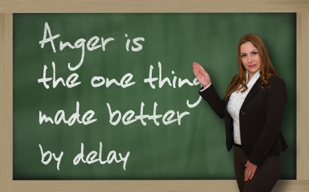 wriiting: Successful, beautiful and confident woman showing Anger is the one thing made better by delay on blackboard