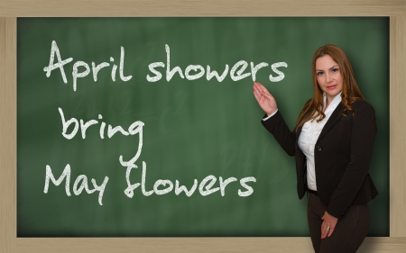april showers: Successful, beautiful and confident woman showing April showers bring May flowers on blackboard