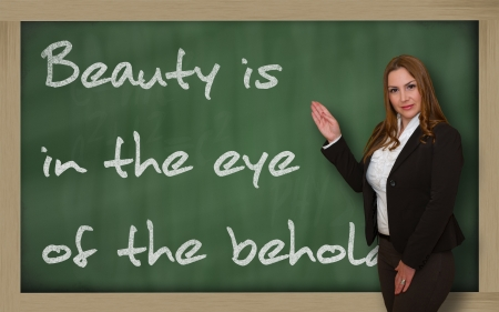 wriiting: Successful, beautiful and confident woman showing Beauty is in the eye of the beholder on blackboard