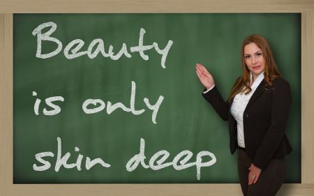 inner beauty: Successful, beautiful and confident woman showing Beauty is only skin deep on blackboard Stock Photo