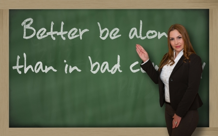 wriiting: Successful, beautiful and confident woman showing Better be alone than in bad company on blackboard