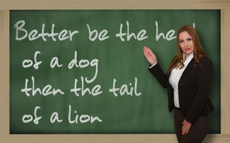 Successful, beautiful and confident woman showing Better be the head of a dog then the tail of a lion on blackboard