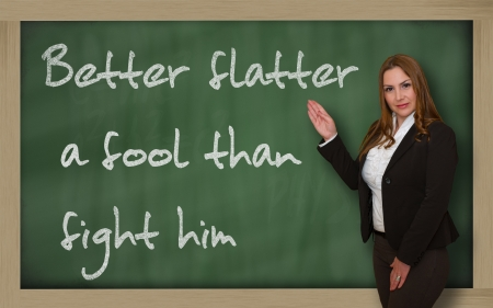 wriiting: Successful, beautiful and confident woman showing Better flatter a fool than fight him on blackboard