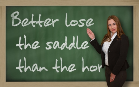 Successful, beautiful and confident woman showing Better lose the saddle than the horse on blackboard