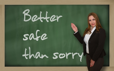 wriiting: Successful, beautiful and confident woman showing Better safe than sorry on blackboard