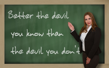 Successful, beautiful and confident woman showing Better the devil you know than the devil you on blackboard Stock Photo