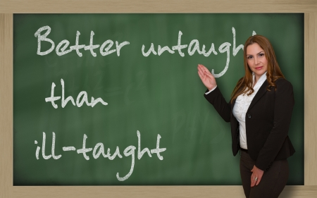 Successful, beautiful and confident woman showing Better untaught than ill-taught on blackboard Stock Photo - 18660462