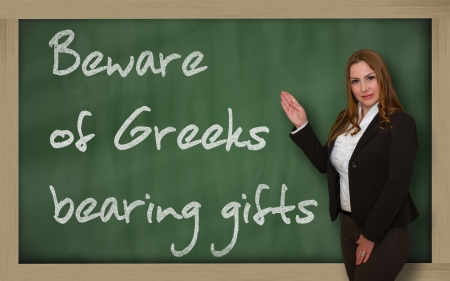 Successful, beautiful and confident woman showing Beware of Greeks bearing gifts on blackboard