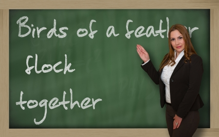 wriiting: Successful, beautiful and confident woman showing Birds of a feather flock together on blackboard Stock Photo