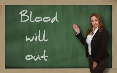 Successful, beautiful and confident woman showing Blood will out on blackboard