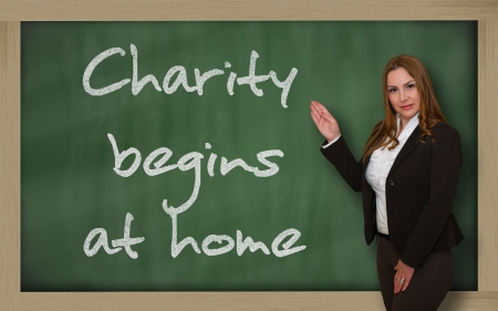wriiting: Successful, beautiful and confident woman showing Charity begins at home on blackboard