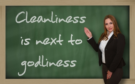 cleanliness: Successful, beautiful and confident woman showing Cleanliness is next to godliness on blackboard