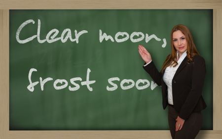 wriiting: Successful, beautiful and confident woman showing Clear moon, frost soon on blackboard