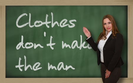 deceiving: Successful, beautiful and confident woman showing Clothes dont make the man on blackboard