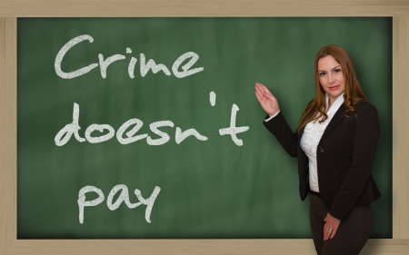 wriiting: Successful, beautiful and confident woman showing Crime doesnt pay on blackboard