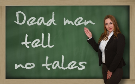 wriiting: Successful, beautiful and confident woman showing Dead men tell no tales on blackboard