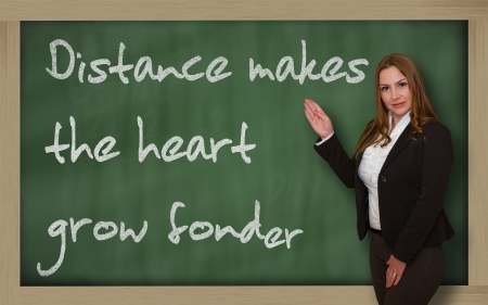 wriiting: Successful, beautiful and confident woman showing Distance makes the heart grow fonder on blackboard