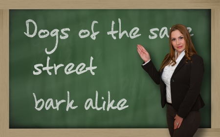 wriiting: Successful, beautiful and confident woman showing Dogs of the same street bark alike on blackboard