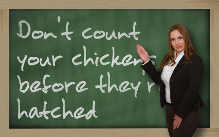 wriiting: Successful, beautiful and confident woman showing Dont count your chickens before theyre hatched on blackboard