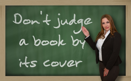 wriiting: Successful, beautiful and confident woman showing Dont judge a book by its cover on blackboard Stock Photo