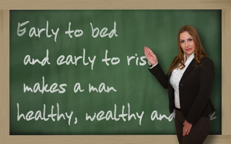 wealthy lifestyle: Successful, beautiful and confident woman showing Early to bed and early to rise makes a man on blackboard Stock Photo