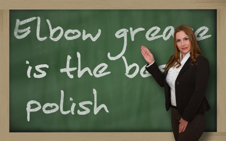 Successful, beautiful and confident woman showing Elbow grease is the best polish on blackboard