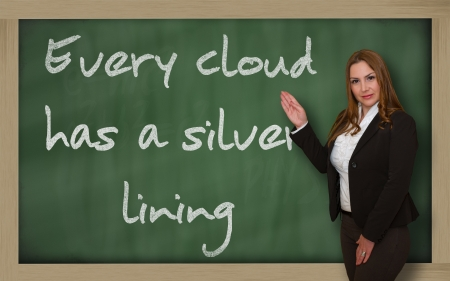 has: Successful, beautiful and confident woman showing Every cloud has a silver lining on blackboard