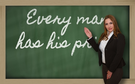 has: Successful, beautiful and confident woman showing Every man has his price on blackboard Stock Photo