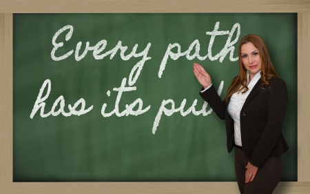 has: Successful, beautiful and confident woman showing Every path has its puddle on blackboard